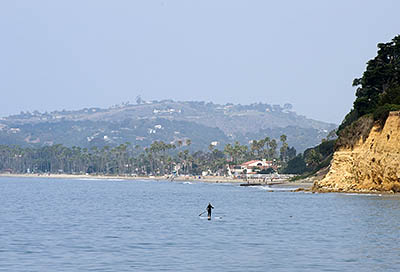 CA: South Coast Region, Santa Barbara County, Pacific Coast Area, City of Santa Barbara, Butterfly Beach, View towards cliffs, with a stand up paddle surfer. [Ask for #271.004.]