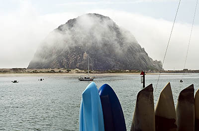 CA: South Coast Region, San Luis Obispo County, Pacific Coast Area, City of Morro Bay, Embarcadero, View across Morro Bay to Morro Rock, wreathed in clouds; rental kayaks. [Ask for #271.011.]
