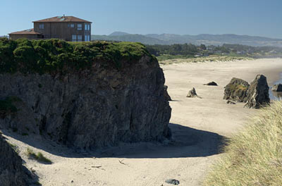 OR: South Coast Region, Coos County, Bandon Area, South Beaches, Face Rock State Wayside, House sits atop sheer rock cliffs with a wide sandy beach below, spotted with large hoodoos [Ask for #274.353.]