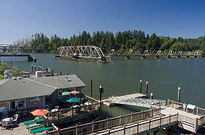 OR: Douglas County, Pacific Coast, Reedsport Area, Boardwalk, View over the Umpqua River towards the Coos Bay Rail Link steel truss drawbridge in open position; restaurant on the boardwalk [Ask for #274.533.]