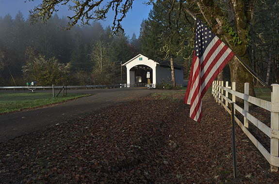 OR: Lane County, South Willamette Valley, Eugene Area, Earnest Covered Bridge. Covered bridge on a well-traveled lane, still carrying traffic. American flag. [Ask for #277.409.]